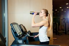 Pretty girl working out in a treadmill at the gym and smiling Stock Photos