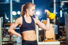 Fitness woman exercising crossfit holding kettlebell strength training biceps Kuvituskuvat