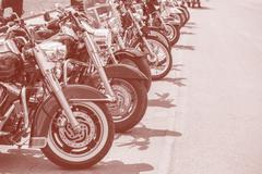 Motobikes in a row on sepia Stock Photos
