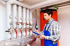 heating engineer in the boiler room - stock photo
