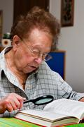 Elderly woman reads a book with glasses Stock Photos