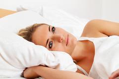 Woman lies awake in bed. Stock Photos