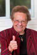 Successful senior citizen laughs with thumbs up Stock Photos