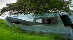 Old Fishing boat in windy grass along the shoreline Stock Footage