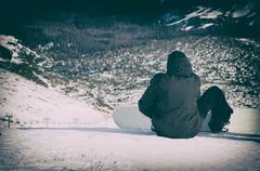 Snowboarder sitting with mountain chain in the background - stock photo