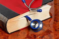 stethoscope is located in a medical book - stock photo
