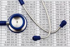 balance sheet figures and stethoscope - stock photo
