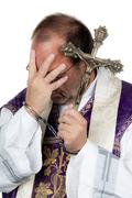 catholic priest in handcuffs. abuse - stock photo