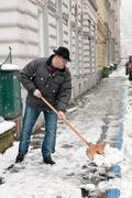 caretaker admits sidewalk of snow - stock photo