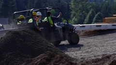 Construction workers driving utility vehicle to job site Stock Footage