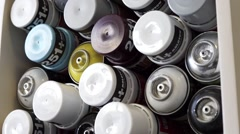 Slowly panning down loads of stacked spraycans in different colors Stock Footage