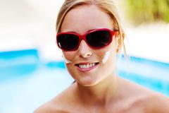 woman with sunglasses and sun cream - stock photo