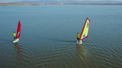 Two windsurfers sailing on lake with birds in background aerial shot Stock Footage