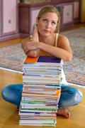 student with a stack of books and computers - stock photo