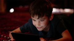 Young boy engrossed in playing games on a touchscreen tablet Stock Footage