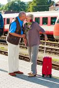 older elderly couple at the railway station - stock photo