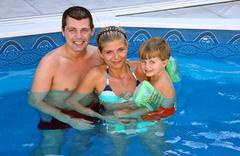 young family in the pool - stock photo