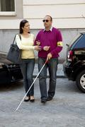 woman helps blind man - stock photo