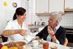 Nurse helps elderly woman at breakfast Stock Photos