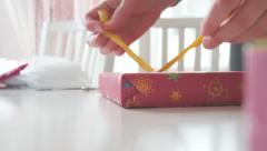 Close-up of woman tying bow on gift box - stock footage