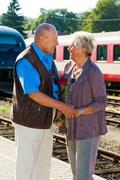Older elderly couple at the railway station Kuvituskuvat