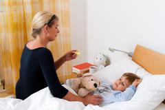 Mother and sick child in bed. flu. kinderkra Stock Photos