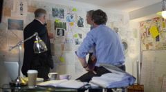 4K Police detectives working together in incident room to try and solve a case Stock Footage