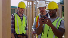 Group of construction workers taking selfies and goofing off with cell phone - stock footage