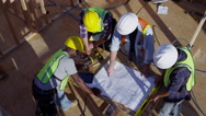 Overhead shot of construction workers lookin at plans - stock footage