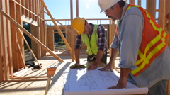 Construction workers looking over plans together Stock Footage