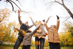 Happy family playing with autumn leaves in park Stock Photos