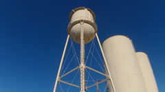 Low Angle Water Towers In Small Town- Slow Zoom Stock Footage