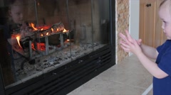 Boy by a fire in the living room dolly shot Stock Footage