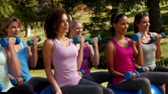 In high quality format fitness group lifting hand weights in park Stock Footage