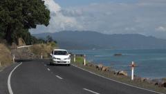Cars drive round bend on coast road, Coromandel Peninsular, New Zealand Stock Footage