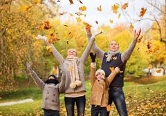 happy family playing with autumn leaves in park - stock photo