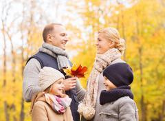 Happy family in autumn park Stock Photos