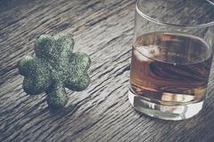 Glass of Whiskey and Clovers to celebrate St Patrick's Day with Retro Instagr Stock Photos