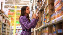 Young woman is choosing food for her child in shopping center. HD. 1920x1080 Stock Footage
