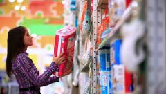 Young woman is shopping in supermarket. She chooses her baby diapers In store - stock footage