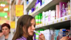 Young man is shopping in supermarket. She chooses perfume In small Perfume shop Stock Footage
