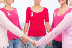 close up of women with cancer awareness ribbons - stock photo