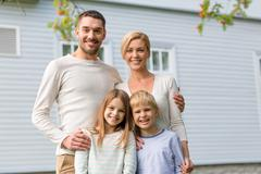 Happy family in front of house outdoors Stock Photos