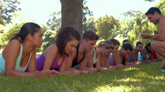 Stock Video Footage of In high quality format fitness group planking in park with coach