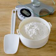 Bread flour in white bowl with rubber scraper and scale on wood table ready t - stock photo