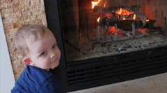 Toddler by a fire in the living room dolly Stock Footage
