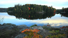Fall colors reflections on tranquil lake in northern Ontario Stock Footage