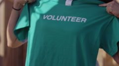 Closeup shot of volunteer passing out t-shirts - stock footage