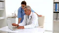 In slow motion doctor using computer keyboard at desk Stock Footage