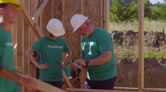 Volunteers working together cutting wood - stock footage
